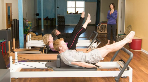 Students strengthening their core with equipment pilates