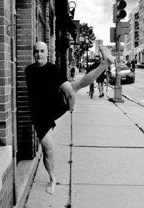 Chris Livanos in a yoga pose on Monroe Street in Madison, WI