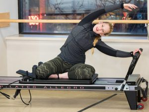 Erica Pinigis pictured on Pilates reformer, certified in STOTT PILATES®, Total Barre, and CORE (HIIT)