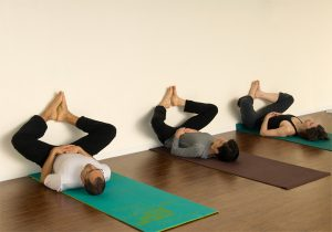 three meditating with feet on wall