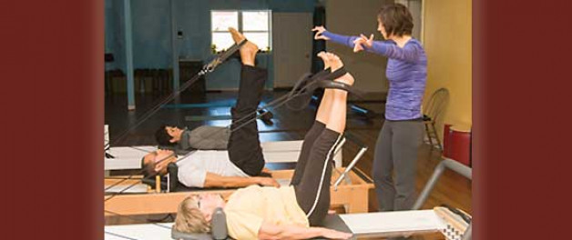 Jules Wolf helping students on Pilates Equipment